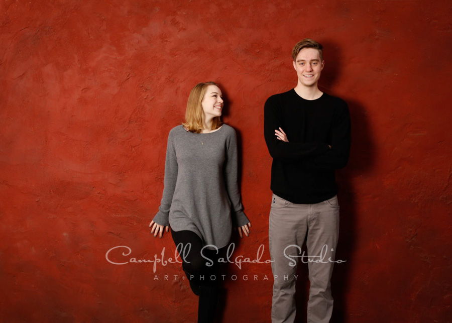 Portrait of siblings on red stucco background by family portrait photographers at Campbell Salgado Studio in Portland, Oregon.