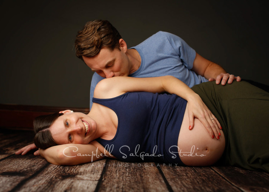 Maternity portrait of couple on grey background by maternity photographers at Campbell Salgado Studio in Portland, Oregon.