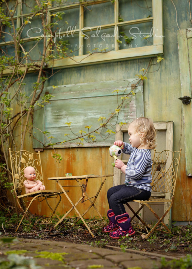 Portrait of toddler on vintage green doors background by child photographers at Campbell Salgado Studio in Portland, Oregon.