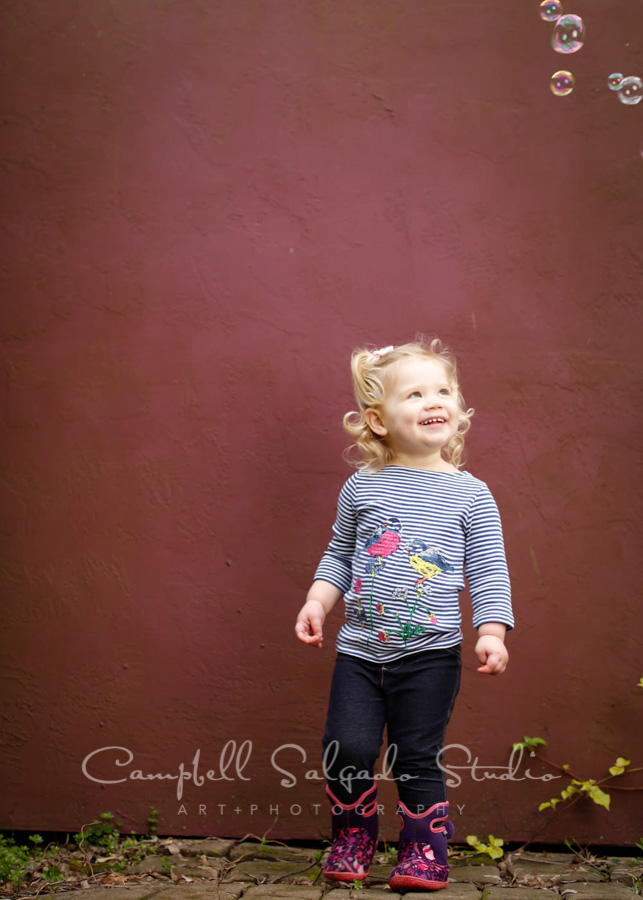 Portrait of toddler on plum stucco background by child photographers at Campbell Salgado Studio in Portland, Oregon.