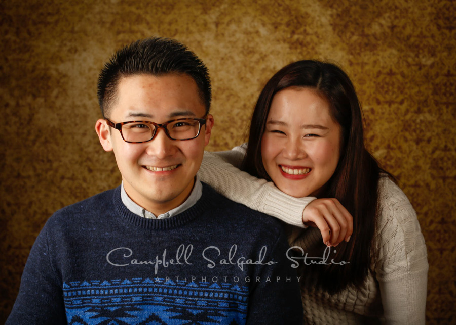 Portrait of couple on amber light background by couple's photographers at Campbell Salgado Studio in Portland, Oregon.