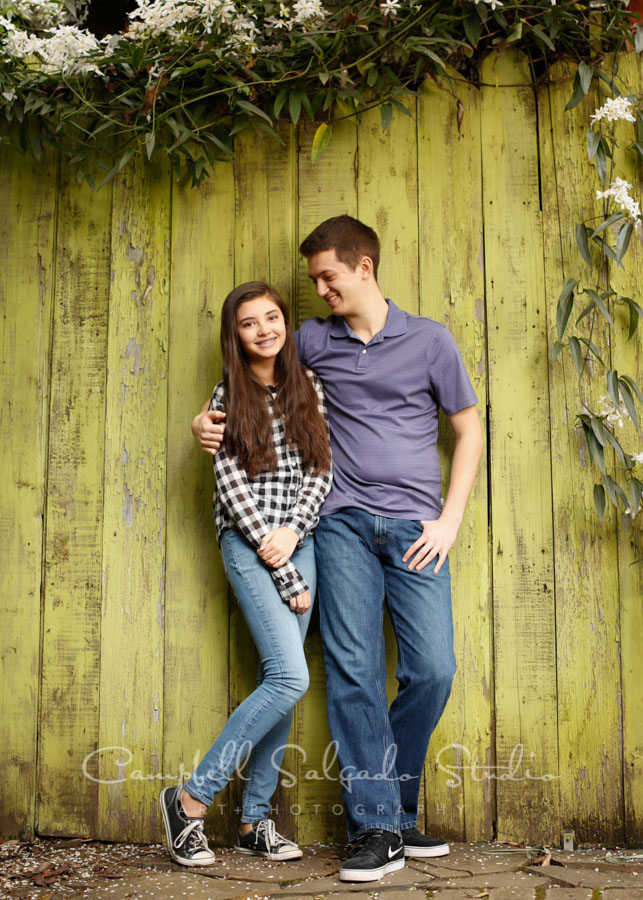 Portrait of teens on lime fenceboards background by family photographers at Campbell Salgado Studio in Portland, Oregon.