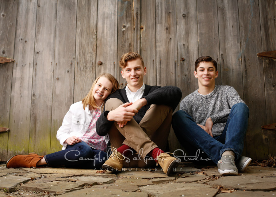 Portrait of siblings on barn door background by family photographers at Campbell Salgado Studio in Portland, Oregon.