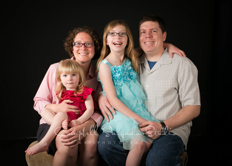 Portrait of family on black background by family photographers at Campbell Salgado Studio in Portland, Oregon.