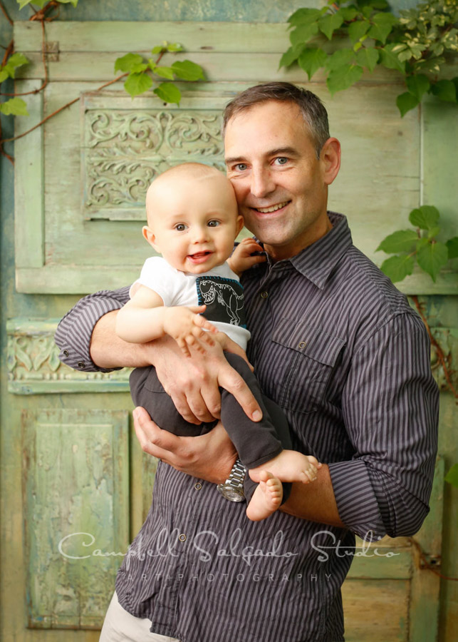 Portrait of father and son on vintage green doors background by family photographers at Campbell Salgado Studio.