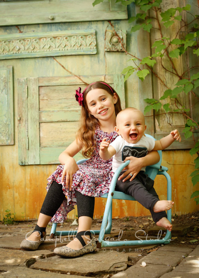 Portrait of siblings on vintage green doors background by children's photographers at Campbell Salgado Studio.