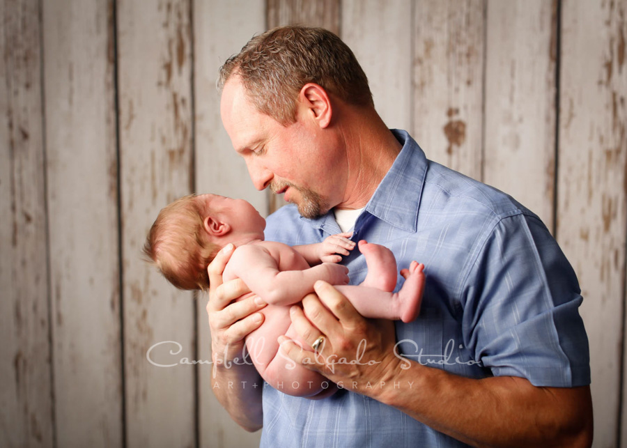 Portrait of father and infant son on white fenceboards background by newborn photographers at Campbell Salgado Studio in Portland, Oregon.