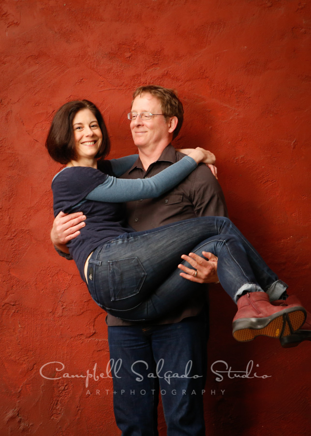 Portrait of couple on red stucco background by couples photographers at Campbell Salgado Studio.