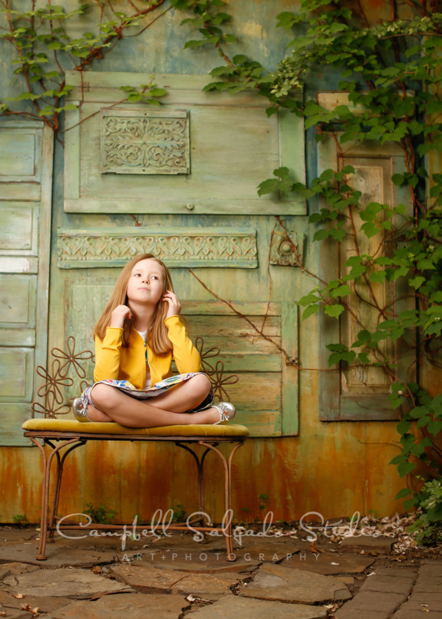 Portrait of girl on vintage green doors background by child photographers at Campbell Salgado Studio in Portland, Oregon.