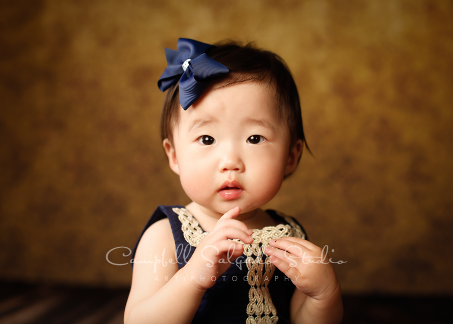 Portrait of baby girl on amber light background by child photographers at Campbell Salgado Studio in Portland, Oregon.