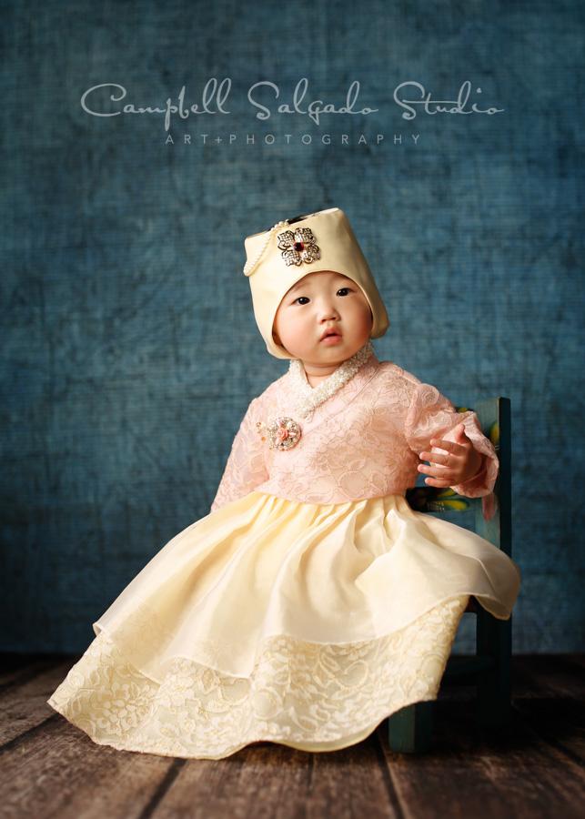Portrait of baby girl on denim background by child photographers at Campbell Salgado Studio in Portland, Oregon.