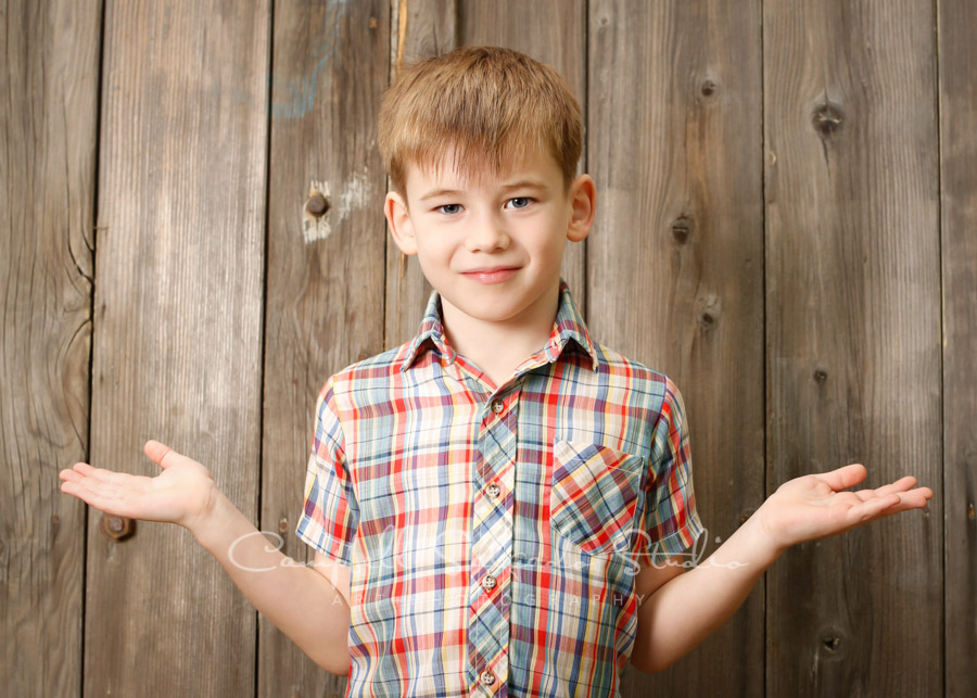 Portrait of boy on barn doors background by family photographers at Campbell Salgado Studio in Portland, Oregon.