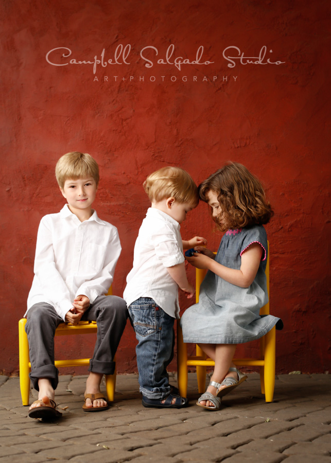 Portrait of kids on red stucco background by family photographers at Campbell Salgado Studio in Portland, Oregon.