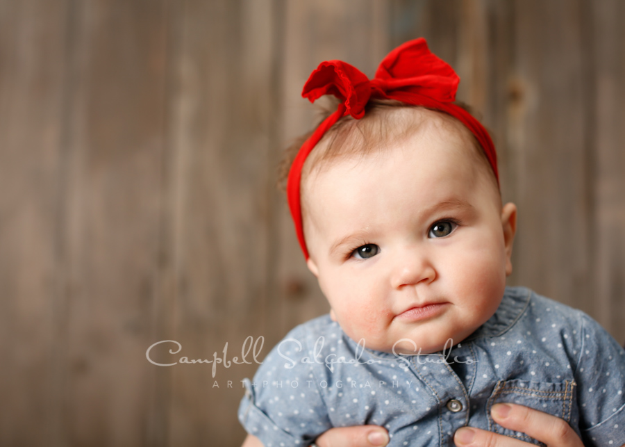 Portrait of baby on barn doors background by child photographers at Campbell Salgado Studio in Portland, Oregon.