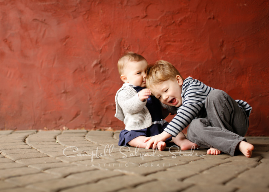 Portrait of children on red stucco background by child photographers at Campbell Salgado Studio in Portland, Oregon.