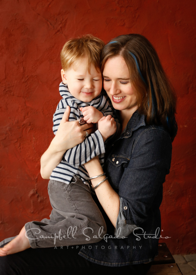 Portrait of mother and son on red stucco background by family photographers at Campbell Salgado Studio in Portland, Oregon.