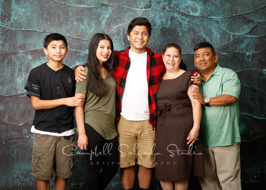 Portrait of family on copper wave background by family photographers at Campbell Salgado Studio in Portland, Oregon.