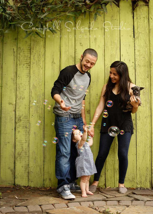 Portrait of family on lime fenceboards background by family photographers at Campbell Salgado Studio in Portland, Oregon.
