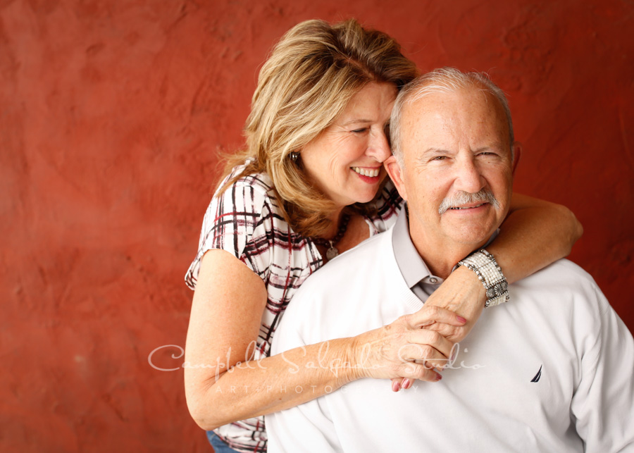 Portrait of couple on red stucco background by couple photographers at Campbell Salgado Studio in Portland, Oregon.