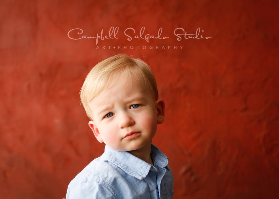 Portrait of child on red stucco background by child photographers at Campbell Salgado Studio in Portland, Oregon.