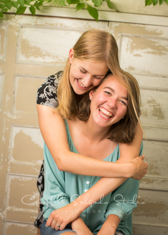 Portrait of sisters on antique white doors background by teen photographers at Campbell Salgado Studio in Portland, Oregon.