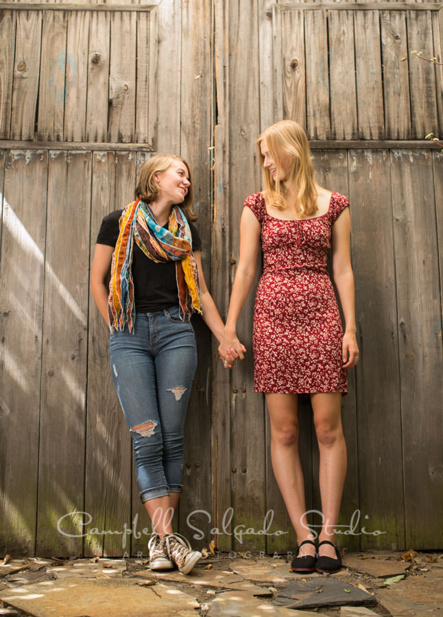 Portrait of sisters on barn doors background by teen photographers at Campbell Salgado Studio in Portland, Oregon.