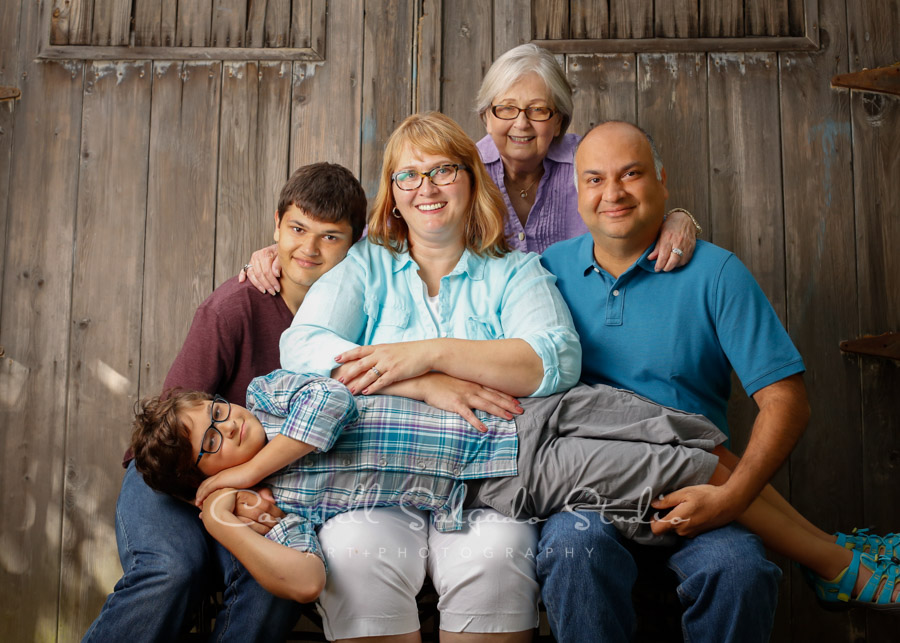 Portrait of multi-generational family on barn doors background by family photographers at Campbell Salgado Studio in Portland, Oregon.