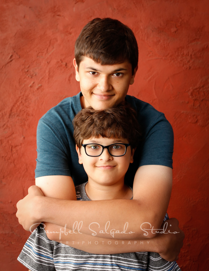 Portrait of brothers on red stucco background by child photographers at Campbell Salgado Studio in Portland, Oregon.