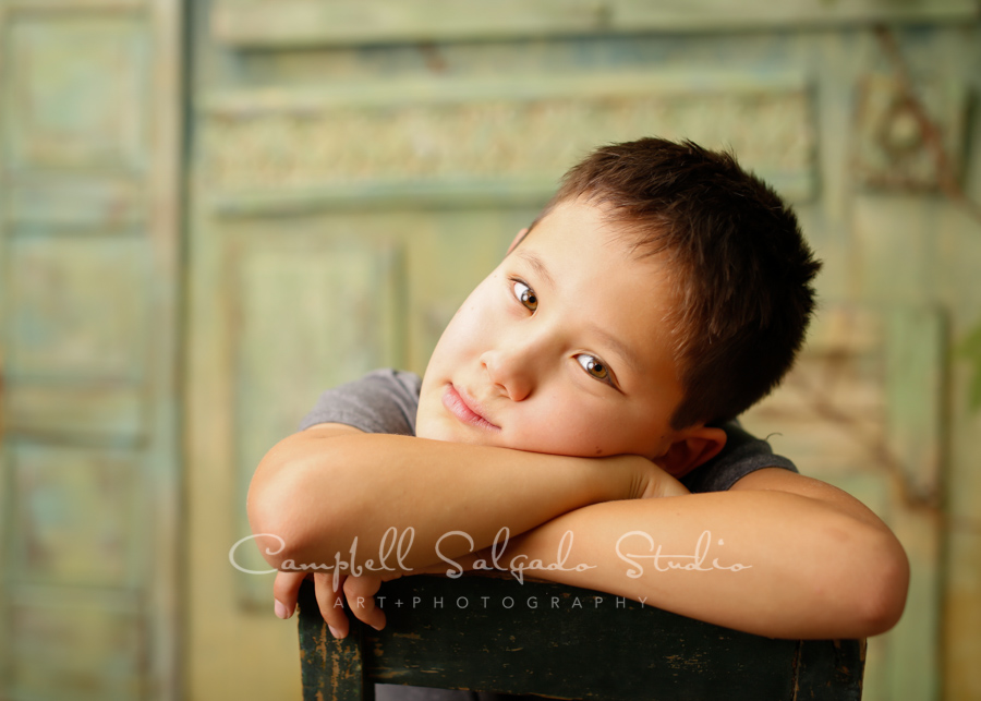 Portrait of boy on vintage green doors background by childrens photographers at Campbell Salgado Studio in Portland, Oregon.