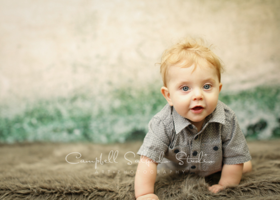 Portrait of baby on weathered green background by child's photographers at Campbell Salgado Studio in Portland, Oregon.
