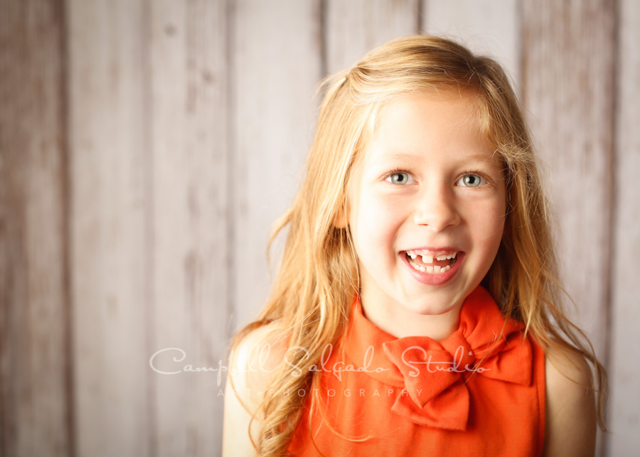 Portrait of girl on white fenceboards background by child photographers at Campbell Salgado Studio in Portland, Oregon.