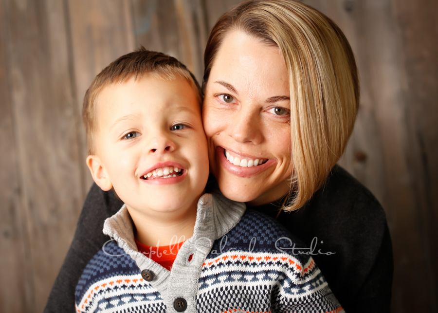 Portrait of family on barn door background by family photographers at Campbell Salgado Studio in Portland, Oregon.