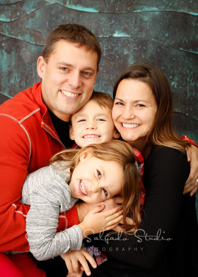 Portrait of family on ocean wave background by family photographers at Campbell Salgado Studio in Portland, Oregon.