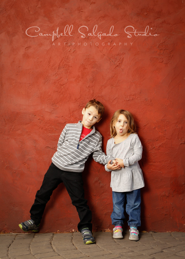 Portrait of kids on red stucco background by child photographers at Campbell Salgado Studio in Portland, Oregon.