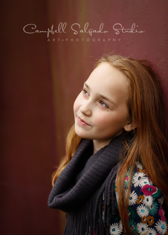 Portrait of girl on plum stucco background by child photographers at Campbell Salgado Studio in Portland, Oregon.