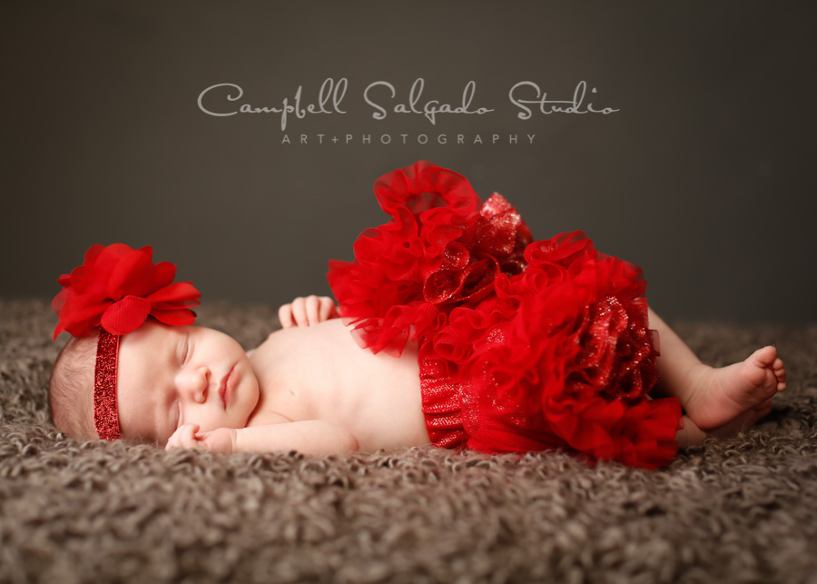 Portrait of infant on grey background by newborn photographers at Campbell Salgado Studio in Portland, Oregon.