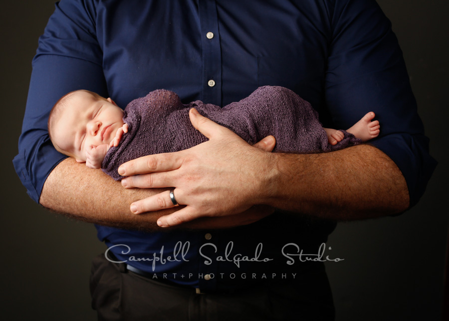 Portrait of infant and father on grey background by newborn photographers at Campbell Salgado Studio in Portland, Oregon.