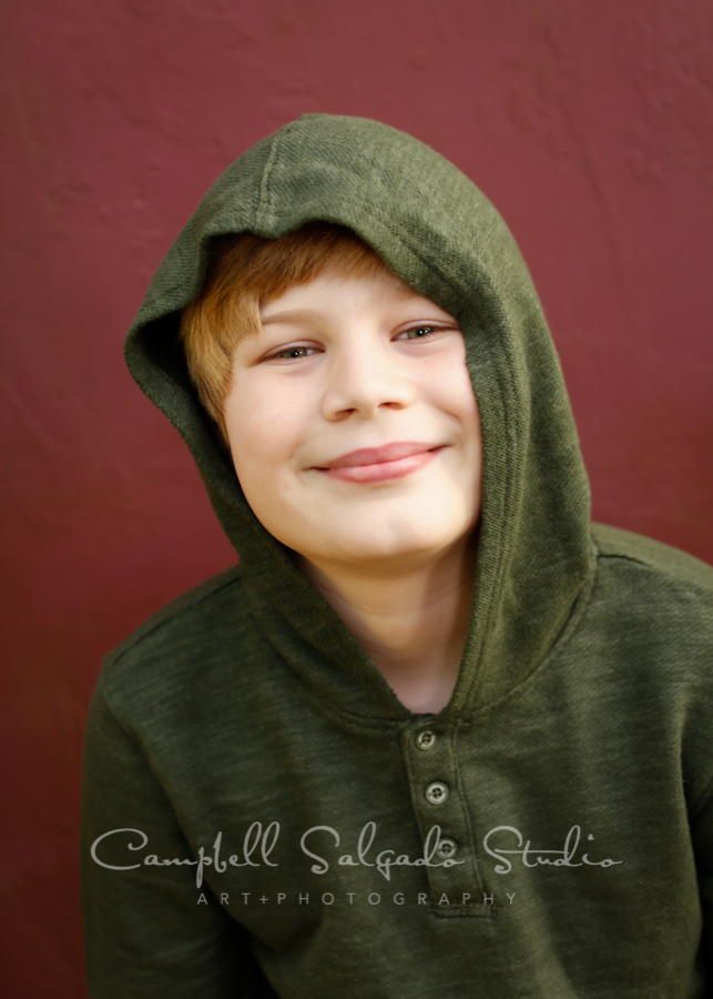 Portrait of boy on plum stucco background by child photographers Campbell Salgado Studio in Portland, Oregon.