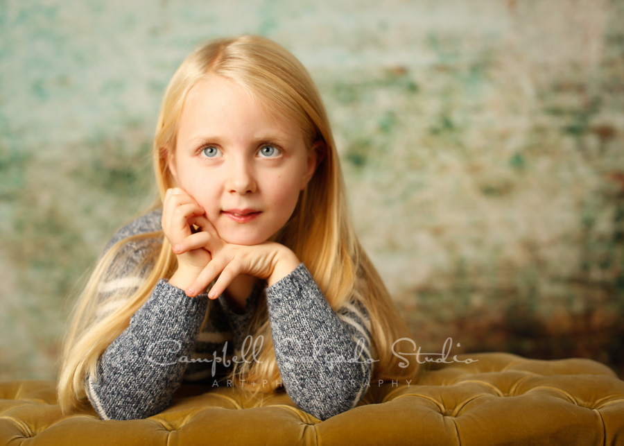 Portrait of girl on weathered green background by children's photographers at Campbell Salgado Studio in Portland, Oregon.