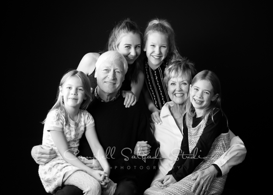 B&W portrait of multi-generational family on black background by family photographers at Campbell Salgado Studio in Portland, Oregon.