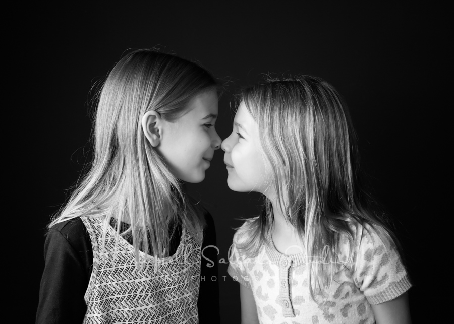B&W portrait of girls on black background by family photographers at Campbell Salgado Studio in Portland, Oregon.