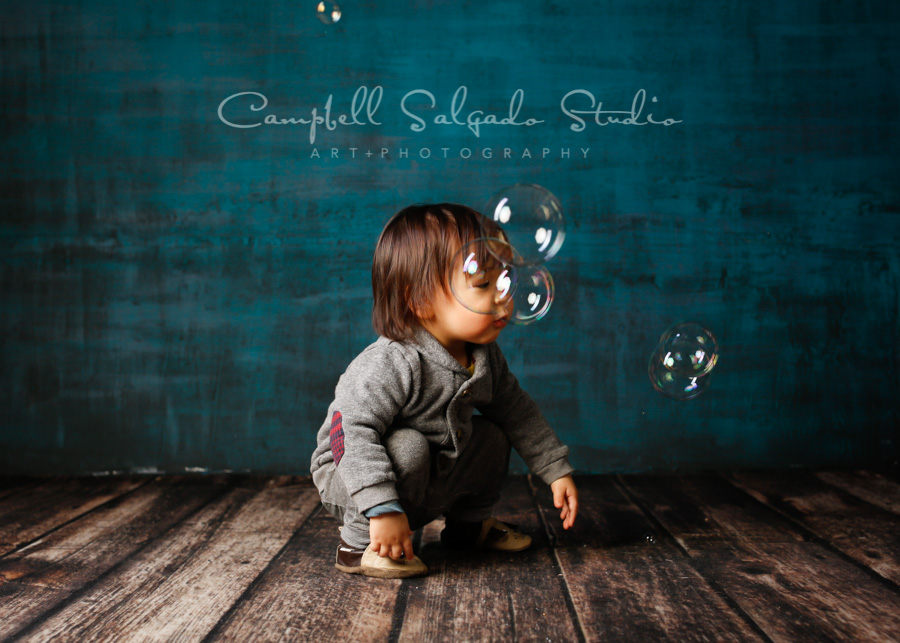 Portrait of baby on deep ocean background by child photographers at Campbell Salgado Studio in Portland, Oregon.