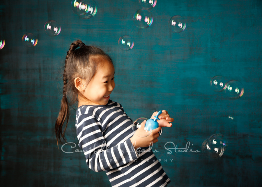 Portrait of boy on deep ocean background by childrens photographers at Campbell Salgado Studio in Portland, Oregon.