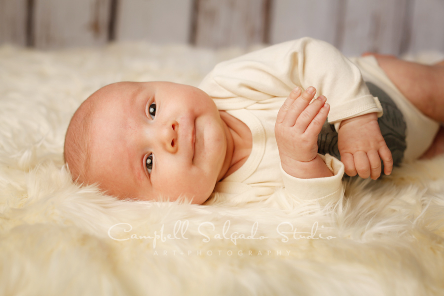 Portrait of baby on white fenceboards background by baby photographers at Campbell Salgado Studio in Portland, Oregon.