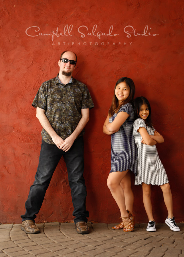Portrait of siblings on red stucco background by family photographers at Campbell Salgado Studio in Portland, Oregon.