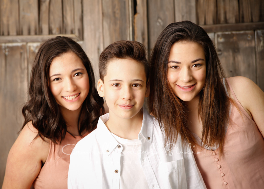 Portrait of siblings on barn doors background by family photographers at Campbell Salgado Studio in Portland, Oregon.