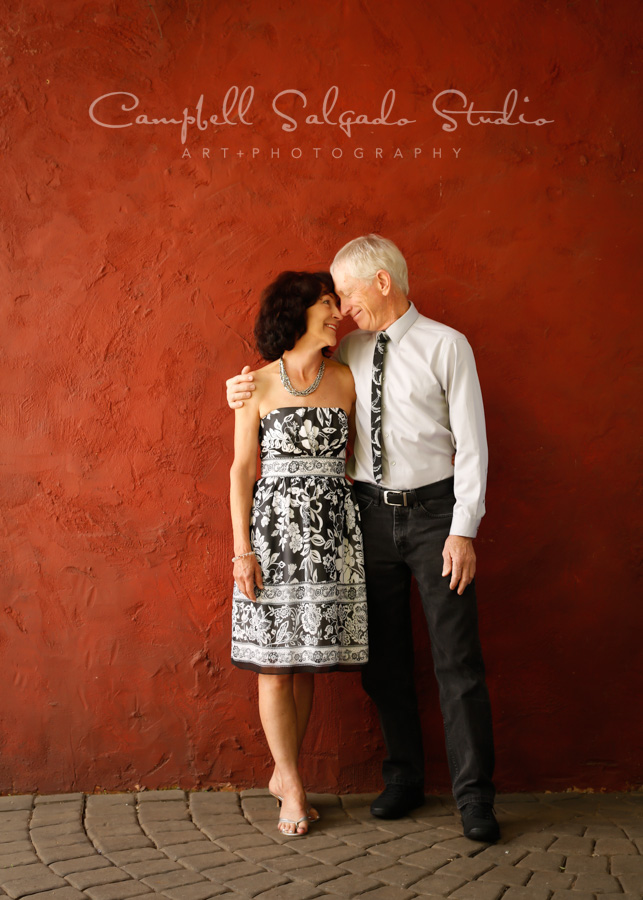 Portrait of couple on red stucco background by couples photographers at Campbell Salgado Studio in Portland, Oregon.
