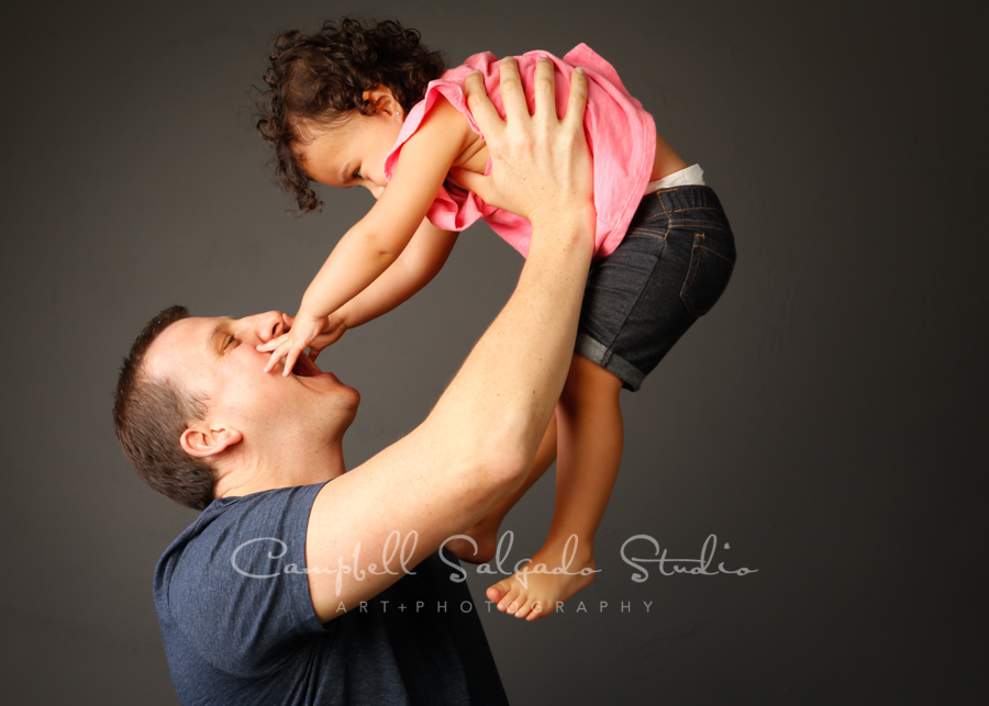 Portrait of father and daughter on gray background by family photographers at Campbell Salgado Studio in Portland, Oregon.