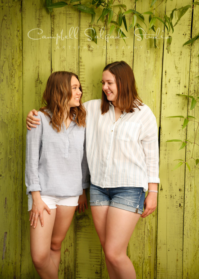 Portrait of teens on lime fence boards background by teen photographers at Campbell Salgado Studio in Portland, Oregon.