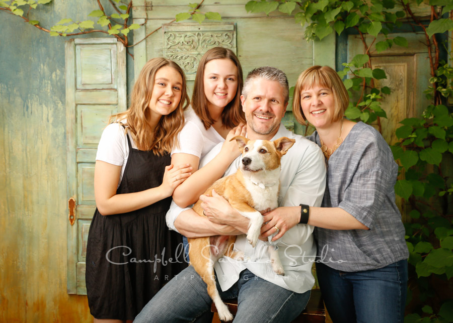 Portrait of family on vintage green doors boards background by family photographers at Campbell Salgado Studio in Portland, Oregon.